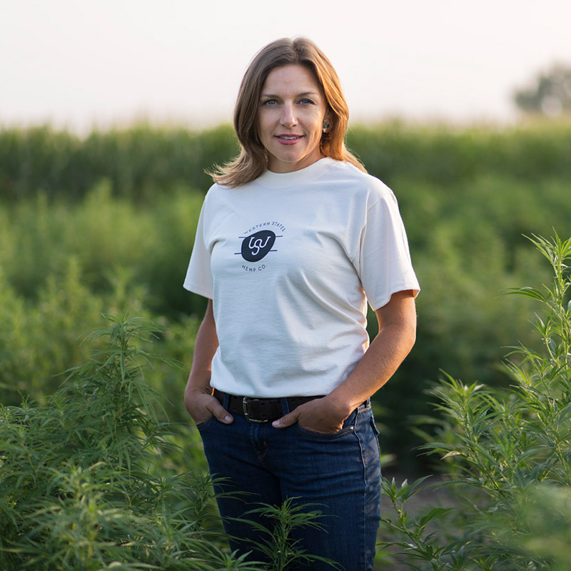 Adrienne Snow standing hemp farm field