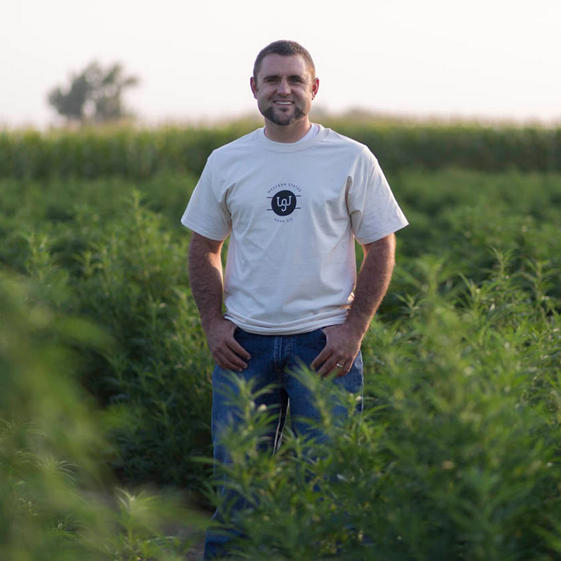 Joe Frey standing hemp farm field